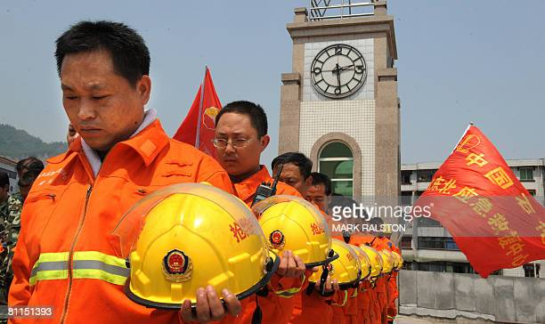 Chinese rescue workers observe three minutes of silence on May 19, 2008 in front of the damaged town clock that stopped after the May 12 earthquake...