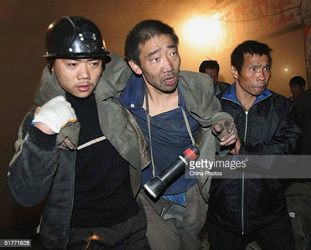 Chinese rescue workers rescue a miner after dozens of workers were trapped underground in a blaze at five iron ore mines on November 21, 2004 in...