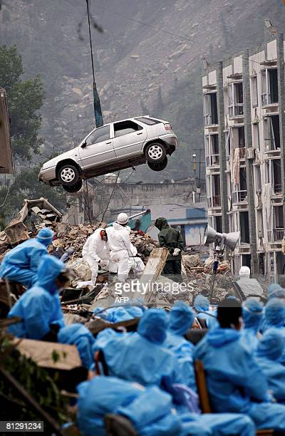 Chinese rescue workers watch as a car is pulled out from the rubble of a collapsed building in Yingxiu southwest China's Sichuan province on May 29...