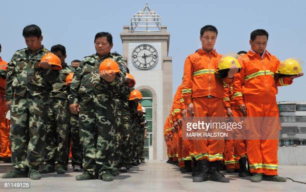 Chinese rescue workes observe three minutes of silence on May 19, 2008 in front of the damaged town clock that stopped after the May 12 earthquake in...