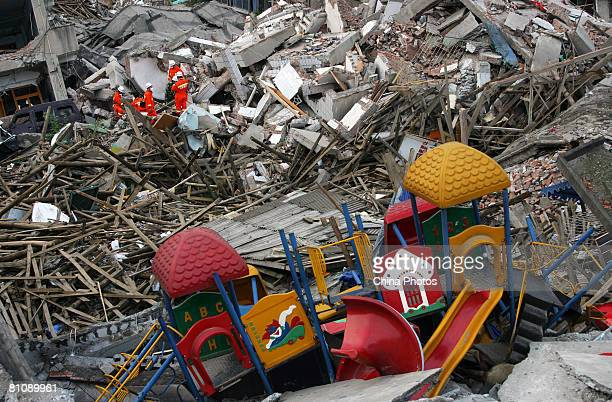 Chinese rescuers and volunteers work on the debris of a collapsed kindergarten in search of earthquake survivors May 14 2008 in Beichuan County...