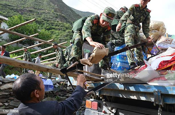 Chinese rescuers help a farmer repair his home after an earthquake on the border with Sichuan province sparked landslides blocked roads trapped...