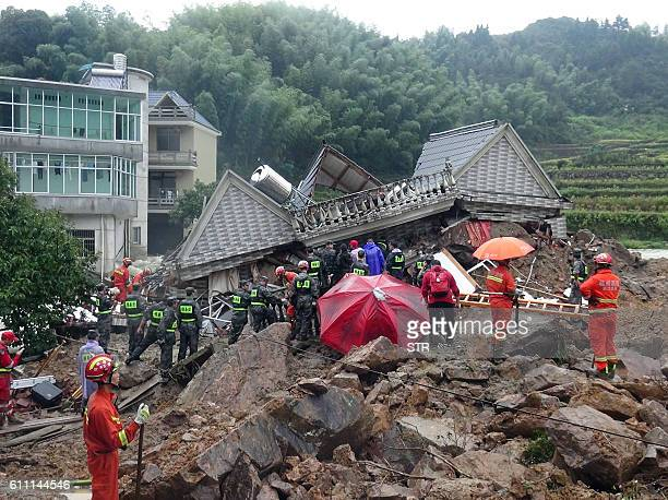 TOPSHOT Chinese rescuers search for survivors at a landslide area in the village of Sucun in Suichang county in China's Zhejiang province on...