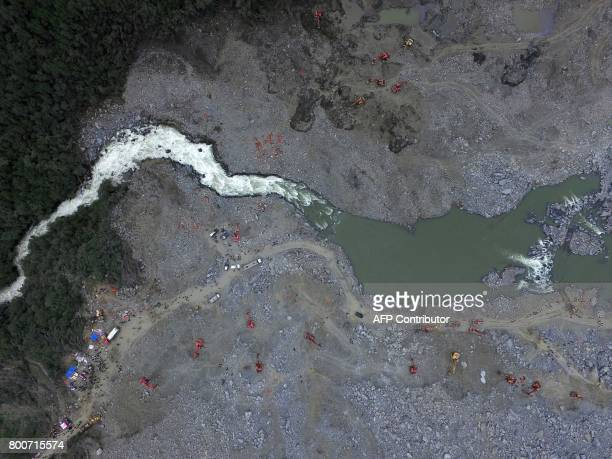 Chinese rescuers search for survivors at a landslide area in the village of Xinmo in Maoxian county China's Sichuan province on June 25 2017 Rescuers...