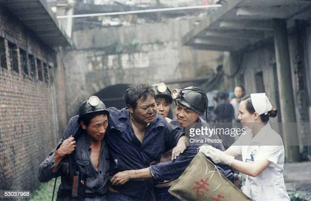 Chinese rescuers support an injured miner as he is evacuated out of a pit after a gas leak at the Zijiang Coal Mine on June 8, 2005 in Loudi of Hunan...