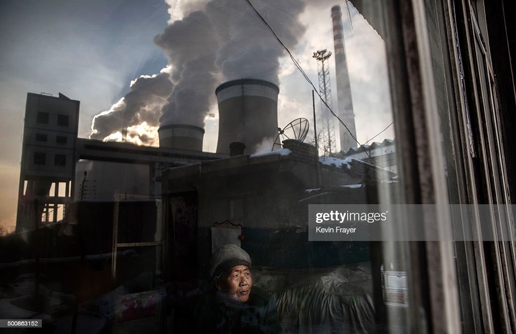 Chinese resident Wang Nu,83, looks out the window of her house next to a coal fired power plant on November 26, 2015 in Shanxi, China. A history of heavy dependence on burning coal for energy has made China the source of nearly a third of the world's total carbon dioxide (CO2) emissions, the toxic pollutants widely cited by scientists and environmentalists as the primary cause of global warming. China's government has publicly set 2030 as a deadline to reach the country's emissions peak, and data suggest the country's coal consumption is already in decline. The governments of more than 190 countries are expected to sign an agreement in Paris to set targets on reducing carbon emissions in an attempt to forge a new global agreement on climate change.