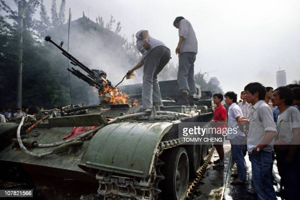 Chinese residents check a burning armoured personnel carrier which was put in on fire by rioters fighting back when the army opened fire on the...