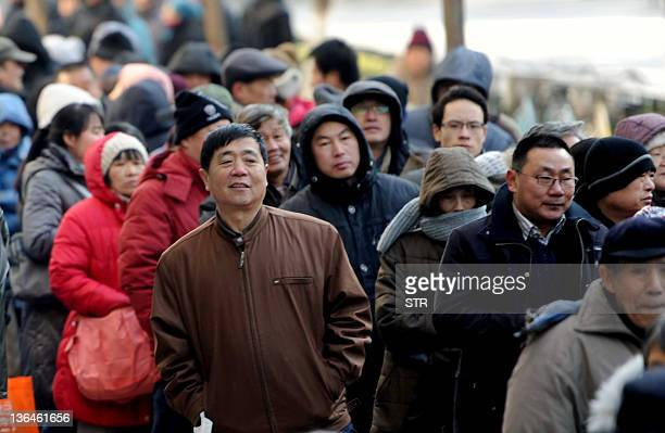Chinese residents queue up to buy Year of the Dragon stamps at a post office in Beijing on January 5, 2012. A new Chinese postage stamp depicting a...
