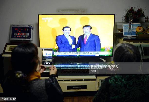 Chinese residents sit in front of the TV at home as they watch live TV coverage of the meeting in Singapore between Chinese President Xi Jinping and...