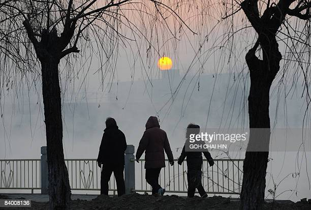 Chinese residents walk along a canal early in the morning in Beijing on December 12 2008 Beijing one of the most polluted cities in the world has...