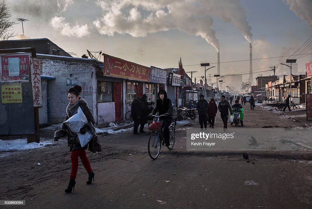 Chinese residents walk in a neighborhood next to a coal fired power plant on November 26, 2015 in Shanxi, China. A history of heavy dependence on burning coal for energy has made China the source of nearly a third of the world's total carbon dioxide (CO2) emissions, the toxic pollutants widely cited by scientists and environmentalists as the primary cause of global warming. China's government has publicly set 2030 as a deadline to reach the country's emissions peak, and data suggest the country's coal consumption is already in decline. The governments of more than 190 countries are expected to sign an agreement in Paris to set targets on reducing carbon emissions in an attempt to forge a new global agreement on climate change.