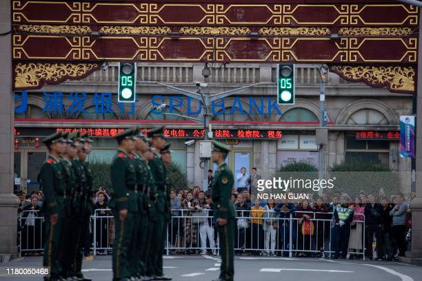 Chinese residents watch as Chinese paramilitary policemen line up in the old city district near the Yu Garden in Shanghai where Chinese President Xi...