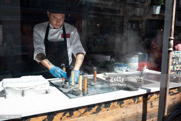 Chinese restaurant chef works in the open kitchen in Chinatown in Soho London United Kingdom The present Chinatown is in the Soho area occupying the...