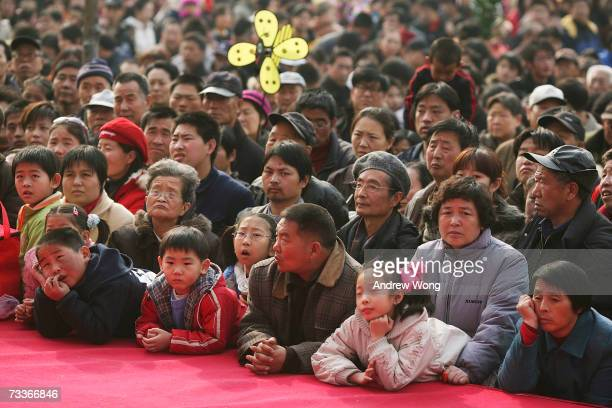 Chinese revellers watch a performance by traditional opera singers at a temple fair to mark the Chinese New Year on February 19 2007 in Beijing China...