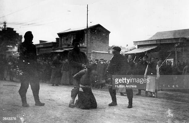 A Chinese revolutionary is summarily beheaded in the street by Imperial troops