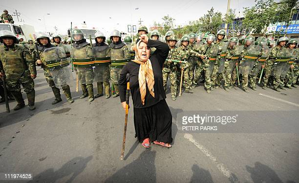 Chinese riot police watch a Muslim ethnic Uighur woman protest in Urumqi in China's far west Xinjiang province on July 7, 2009 following a third day...