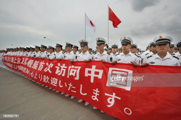 Chinese sailors hold a banner which reads Welcome Japanese Maritime SelfDefense Force vessel's first visit to China as 4650tonne destroyer Sazanami...