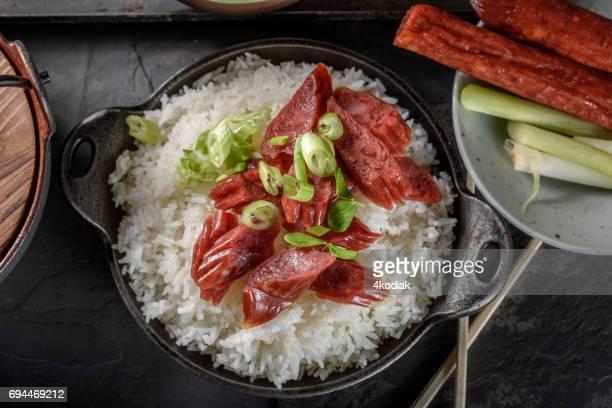 chinese worst over gestoomde rijst in zwarte keramische kom kom - gerookte worst stockfoto's en -beelden