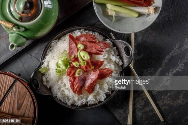 chinese worst over kom gestoomde rijst in gietijzeren kuip - gerookte worst stockfoto's en -beelden