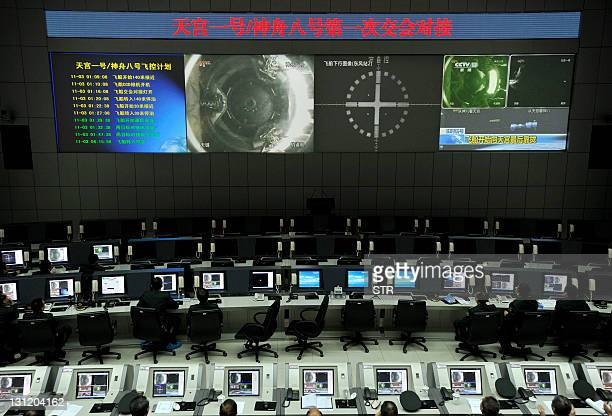 Chinese scientists monitor the docking of the Tiangong1 space lab module and the Shenzhou VIII spacecraft in space at the Jiuquan Satellite Launch...