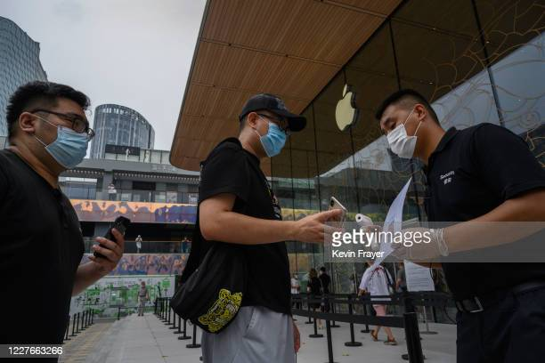 Chinese security guard checks health codes and temperatures of customers entering at the official opening of the new Apple Store in the Sanlitun...