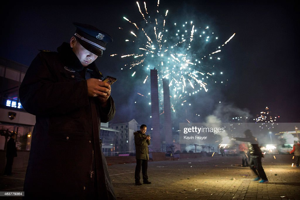 A Chinese security guard checks his smartphone as fireworks explode during celebrations of the Lunar New early on February 19, 2015 in Beijing, China.The Chinese Lunar New Year of Sheep also known as the Spring Festival, which is based on the Lunisolar Chinese calendar, is celebrated from the first day of the first month of the lunar year and ends with Lantern Festival on the Fifteenth day.