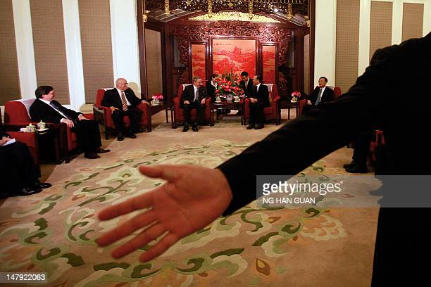 A Chinese security guard motions for journalists to leave after a photo call with Cuban President Raul Castro and Chinese Premier Wen Jiabao during...
