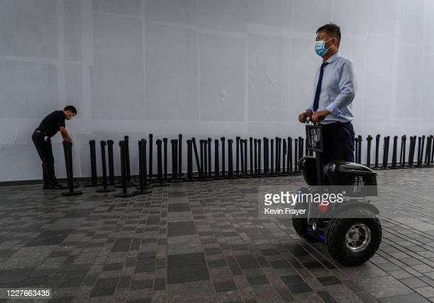 Chinese security guard rides a segway outside the official opening of the new Apple Store in the Sanlitun shopping area on July 17 2020 in Beijing...