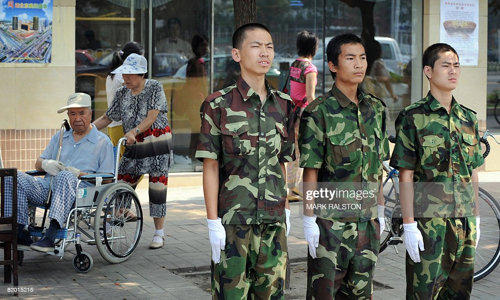 Chinese security guards dressed in military uniforms conduct