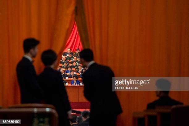 TOPSHOT Chinese security guards look at military delegates during the speech of Chinese President Xi Jinping at the Communist Party's 19th Congress...