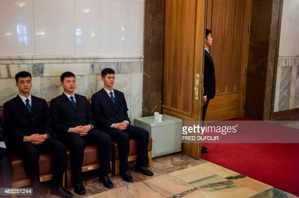 Chinese security guards look on during the opening of the third Session of the 12th National People's Congress at the Great Hall of the People in...