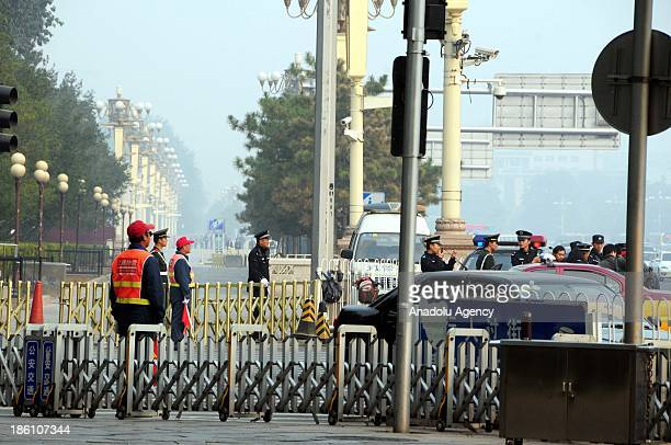 Chinese security guards stand guard at the Tianamen Square Beijing on October 28 2013 5 people died and 38 injured on a car crash after a car...