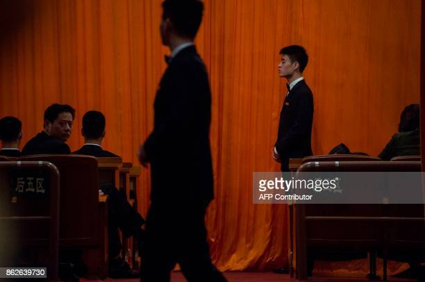 Chinese security guards wait on the back of the plenary during the speech of Chinese President Xi Jinping at the Communist Party's 19th Congress in...