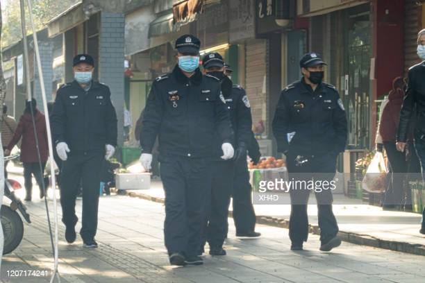 chinese security men wearing surgical mask working on food market - china coronavirus stock pictures, royalty-free photos & images