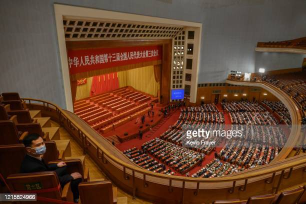 Chinese security officer wears a protective mask as delegates arrive at the closing session of the National People's Congress at the Great Hall of...