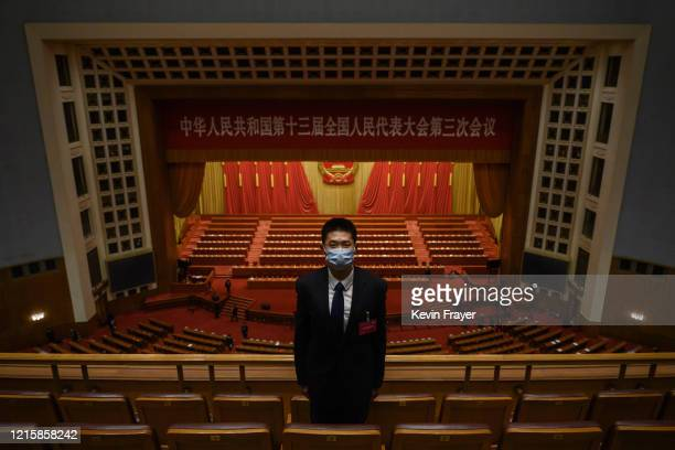 Chinese security officer wears a protective mask as he guards after the closing session of the National People's Congress at the Great Hall of the...