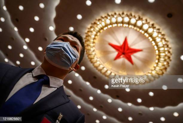 Chinese security officer wears a protective mask at the end of the closing session of the National People's Congress at the Great Hall of the People...