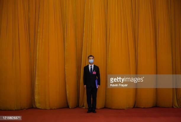 Chinese security officer wears a protective mask before the closing session of the National People's Congress at the Great Hall of the People on May...