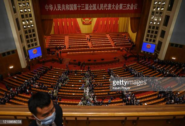 Chinese security officer wears a protective mask while delegates file out after the closing session of the National People's Congress at the Great...