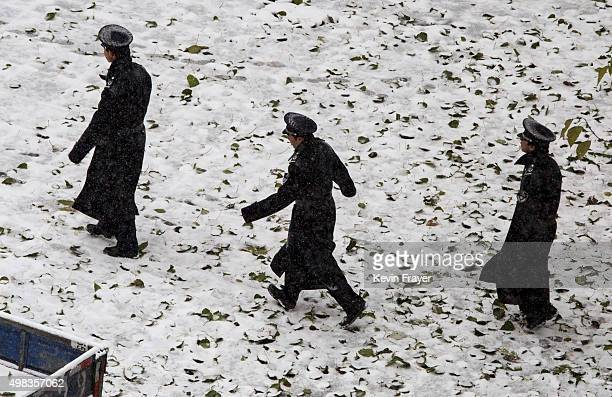 Chinese security officers march through a snow covered parking lot during a snowfall on November 22 2014 in Beijing China China's capital and other...