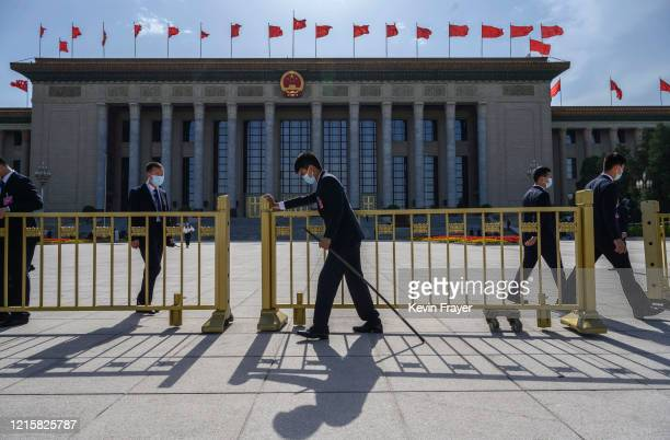 Chinese security officers wear protective masks as they close the gates after the closing session of the National People's Congress at the Great Hall...
