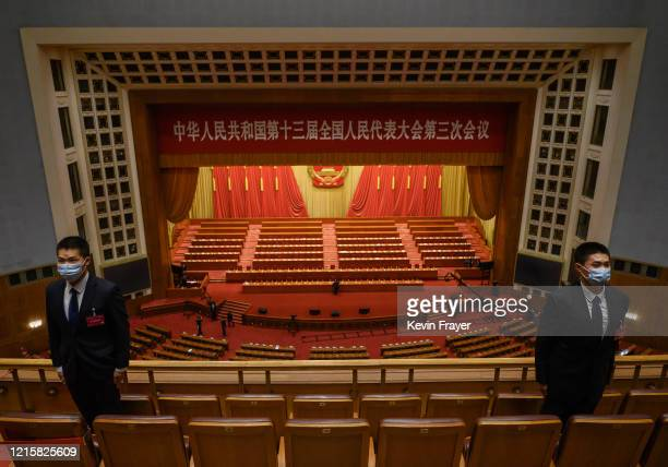 Chinese security officers wear protective masks as they guard after the closing session of the National People's Congress at the Great Hall of the...