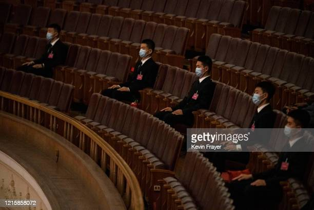 Chinese security officers wear protective masks as they sit before the closing session of the National People's Congress at the Great Hall of the...