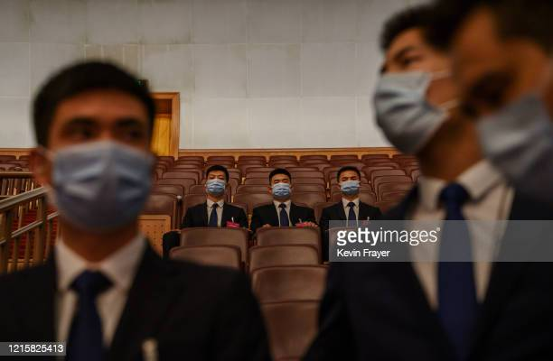 Chinese security officers wear protective masks before the closing session of the National People's Congress at the Great Hall of the People on May...