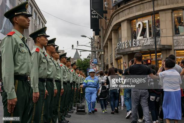Chinese security personnel keep watch as pedestrians walk past during the weeklong 'Golden Week' holidays at a zebra crossing in Shanghai on October...