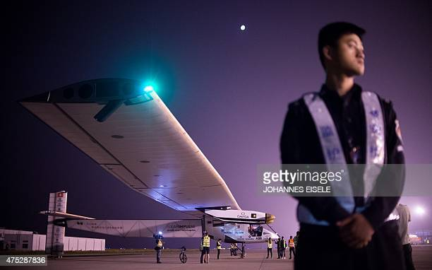 A Chinese security staff member stands guard shortly before the Swissmade solarpowered plane Solar Impluse 2 takes off from Nanjing's Lukou...