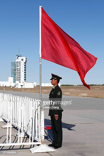 Chinese security stands near a Long March 2F rocket carrying Tiangong1 China's first unmanned space module stands at the Jiuquan Satellite Launch...
