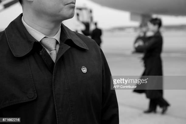 Chinese Security the counterpart to the US Secret Service stands in front of the press at the foot of Air Force One as US President Donald Trump and...