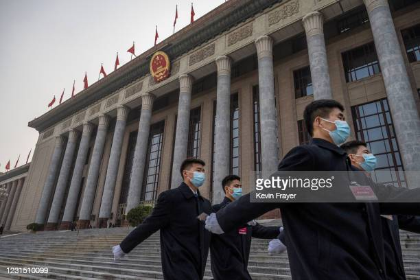 Chinese security wear protective masks as they march after the opening session of the Chinese People's Political Consultative Conference at the Great...