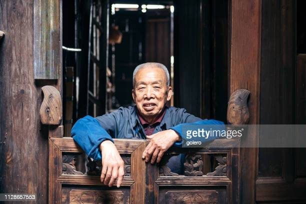 chinese senior man looking out of old wooden house - stringed instrument stock pictures, royalty-free photos & images